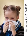 Little girl with the flu having red eyes - blowing nose - stock photo