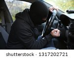 male thief sitting in car | Shutterstock . vector #1317202721