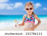 Adorable little girl at tropical beach applying sunblock cream - stock photo