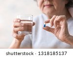 elderly woman taking pill ... | Shutterstock . vector #1318185137
