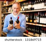 Man in a supermarket choosing the right wine - stock photo