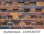 Small photo of Building wall made of dark, yellow to brownish clinker bricks with various alternating patterns. The stones are offset in rows, turned, indented or omitted.
