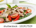 Tuna salad with fresh spinach, cherry tomatoes, white beans and pesto dressing. - stock photo