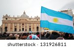 Small photo of ROME, ITALY - MARCH 17: The crowd is waiting in St. Peter Square before the first Angelus prayer of Pope Francis I, A flag of Argentina in foreground, on March 17, 2013 in Vatican City, Rome, Italy