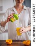 woman making orange juice in... | Shutterstock . vector #1319325857