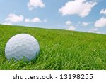 golf ball on grass bunker with blue sky background - stock photo