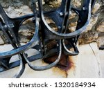 shiny painted black wrought iron decorated ornate steel gate detail with textured light color grunge decaying concrete floor and rusty hinge. detail in the castle district in Budapest. travel concept