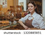 cheerful young female baker... | Shutterstock . vector #1320885851
