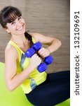 Pretty young girl pump stomach with dumbbells exercises - stock photo