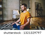 Small photo of Calm young man with closed eyes sitting in lotus pose on comfortable carpet meditating in morning time at home interior.Hipster guy doing yoga to support flexibility and viability every day