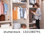 Small photo of Woman choosing outfit from large wardrobe closet with stylish clothes, shoes and home stuff