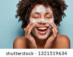 Small photo of Spa, therapy and beauty concept. Satisfied black woman washes face with white soap, has cleansing foam, purification of face, cleans pores, shows bare shoulders, isolated over blue studio wall