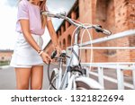 Small photo of Woman in a pink t-shirt near the fence parking in the summer in the park. Locks, locks the cable with a code number. Protection against hijackings and scammers and thieves. Safety bike in the city.