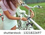 Small photo of Girl in a pink T-shirt near the fence in the summer in the park. Locks, locks the cable with a code number. Protection against hijackings and scammers and thieves. Safety bike in city.