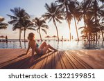 Small photo of tropical getaway retreat in luxury beach hotel, luxury travel, woman relaxing near swimming pool at sunset