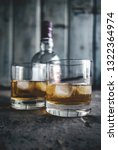 two glasses with whiskey and... | Shutterstock . vector #1322364974