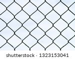 mesh metal fence against the... | Shutterstock . vector #1323153041