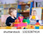 little nursery child boy sits... | Shutterstock . vector #1323287414
