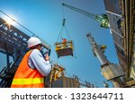 foreman, supervisor, worker, loading master in works at job site, control to the teamwork by walkie talkie radio for job done in the same direction, working at risk and high level of insurance - stock photo