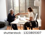 senior woman shaking hands with ... | Shutterstock . vector #1323805307