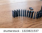 Small photo of black dominocards with white dots in rows and balanced one after the other on a wooden table. Tiles of the domino before falling for a chain effect. Business disaster concept with domino effect