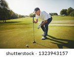 sporty senior man crouching on... | Shutterstock . vector #1323943157