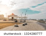 View of Namal promenade at Tel Aviv Port, Israel. Sunset at harbour deck with carousel and sunshades by the sea