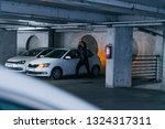 Young man is trying to break the car door on the parking - stock photo
