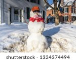 Small photo of Grafton, NY / USA - 03-06-2015: Funny snowman adorned with bucktooth smile, baseball cap, and bottle of beer.