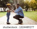 african man putting helmet on... | Shutterstock . vector #1324489277
