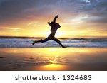 Woman jumps at sunrise - stock photo