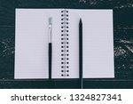 notepad on black wooden desk... | Shutterstock . vector #1324827341