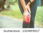 Small photo of Woman holding her knee with red pain on the skeleton
