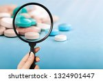 Small photo of Pharmacist or expert on pharmaceutical inspection identifies pills. Testing, verification and determining pharmaceutical counterfeiting or fakes of medicines and medicinal substance quality concept