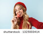 Stock photo image of attractive blond woman s wearing red beret eating macaron biscuit while taking selfie 1325003414