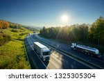 Small photo of Three white trucks and chrome tanker driving on the asphalt highway between deciduous forest under the rays of the sun. View from above.