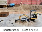 a mini excavator digs a hole in ... | Shutterstock . vector #1325579411