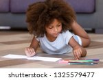 African American little girl drawing with colored pencils on white sheet, playing lying on wooden warm floor in living room at home, preschool child having fun, spending free time alone