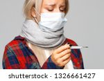 Small photo of Sick young woman in checked shirt, wrapped scarf with fever looking and checking her temperature, feeling illness, soft focus. Weakened immunity, cold, flu season. Body temperature, healthcare concept