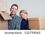 Happy couple in new home holding boxes - stock photo
