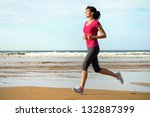 Woman Running On Beach At...