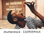 young african man eating pizza... | Shutterstock . vector #1329059414