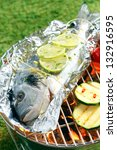 Small photo of Whole fresh gilthead breem garnished with sliced lemon roasting on aluminium foil over the glowing coals in a barbecue