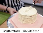 woman frosting a cake on a... | Shutterstock . vector #1329316214