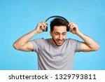 man smiling puts on headphones ...   Shutterstock . vector #1329793811