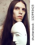 Portrait of a handsome long-haired poet with a white italian (venetian) mask volto bianco waiting for inspiration. Vintage (classic) style. Studio shot. - stock photo