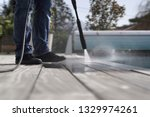 Man using high pressure washer cleaning deck - stock photo