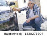 Mature man washing his car with soapy sponge in driveway - stock photo