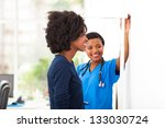 Stock photo friendly african nurse measuring patient s height 133030724