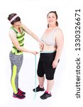 Small photo of Personal female trainer is measuring the waist of a voluptuous woman,isolated o white.